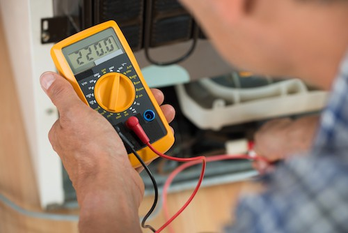 Repairman Checking Fridge With Digital Multimeter