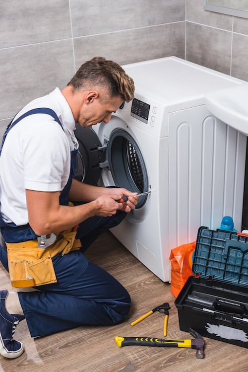 service technician fixing a domestic appliance